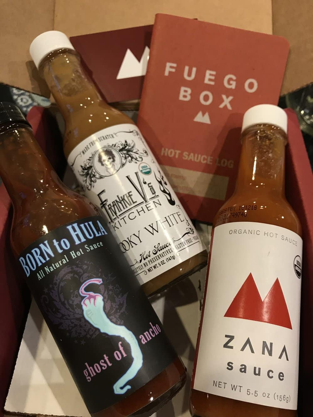 An assortment of three bottles of hot sauce from Fuego Box