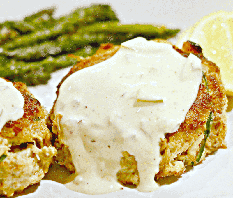 A close up of two crab cakes with tartar sauce on top