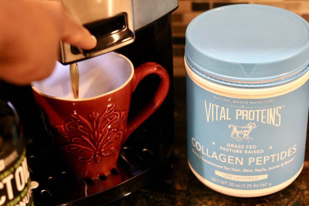 A red cup of coffee within a coffee maker with a container of Vital Proteins Collagen Peptides for Butter Coffee (Bulletproof Coffee)