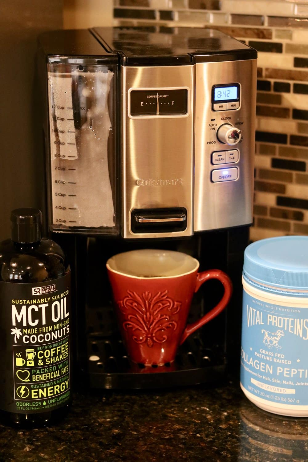 A red cup of coffee in front of a coffee maker with a bottle of Sports Research MCT Oil and a container of Vital Proteins Collagen Peptides for Butter Coffee (Bulletproof Coffee)