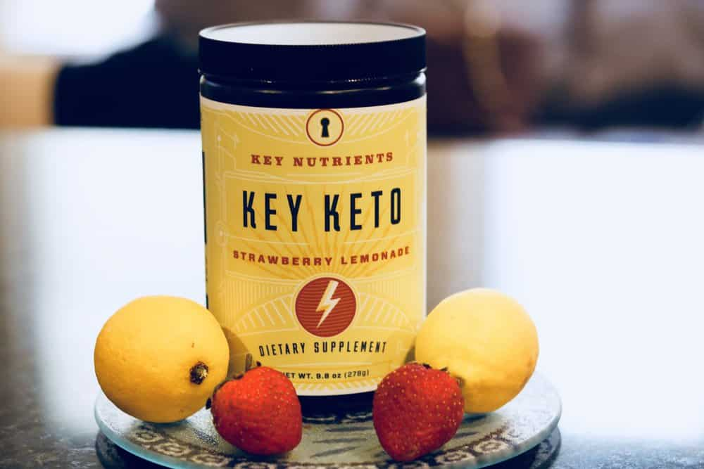 A container of Strawberry Lemonade Key Keto by Key Nutrients, surrounded by strawberries and lemons.