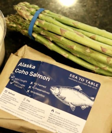 A bundle of asparagus with a package of Salmon