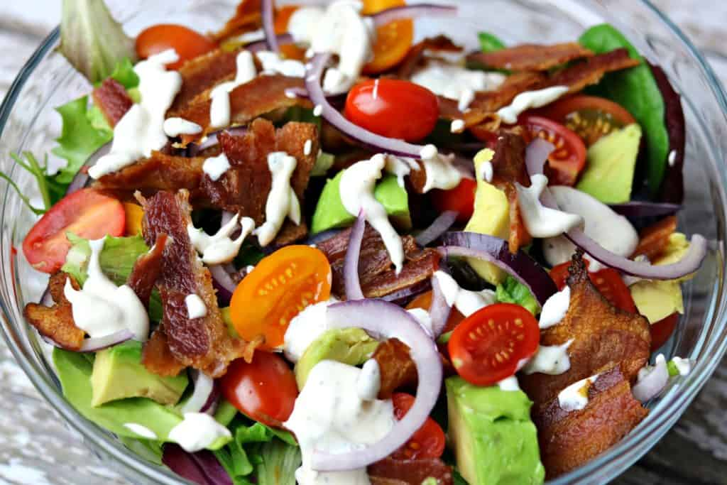BLT Avocado salad in a glass bowl, topped with ranch dressing