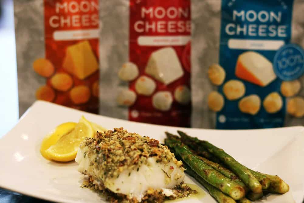 A serving dish with Pecan-Gouda Crusted Cod, asparagus, and slices of lemon in front of three pouches of Moon Cheese products
