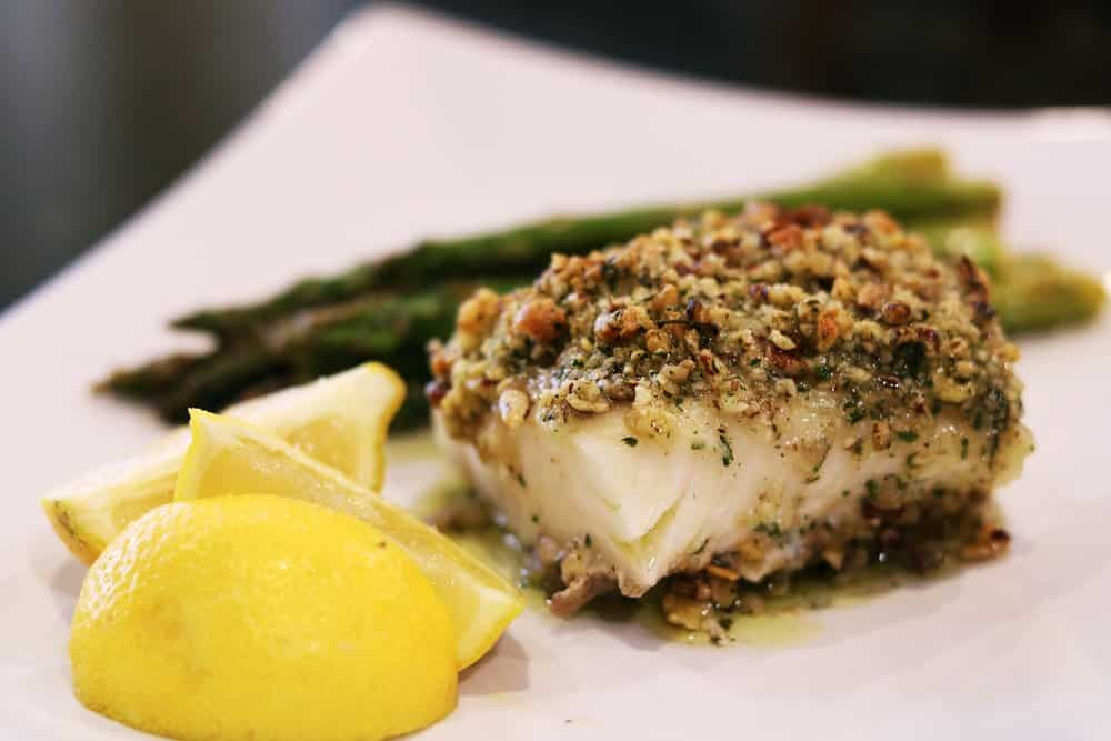 A serving dish with Pecan-Gouda Crusted Cod, asparagus, and slices of lemon