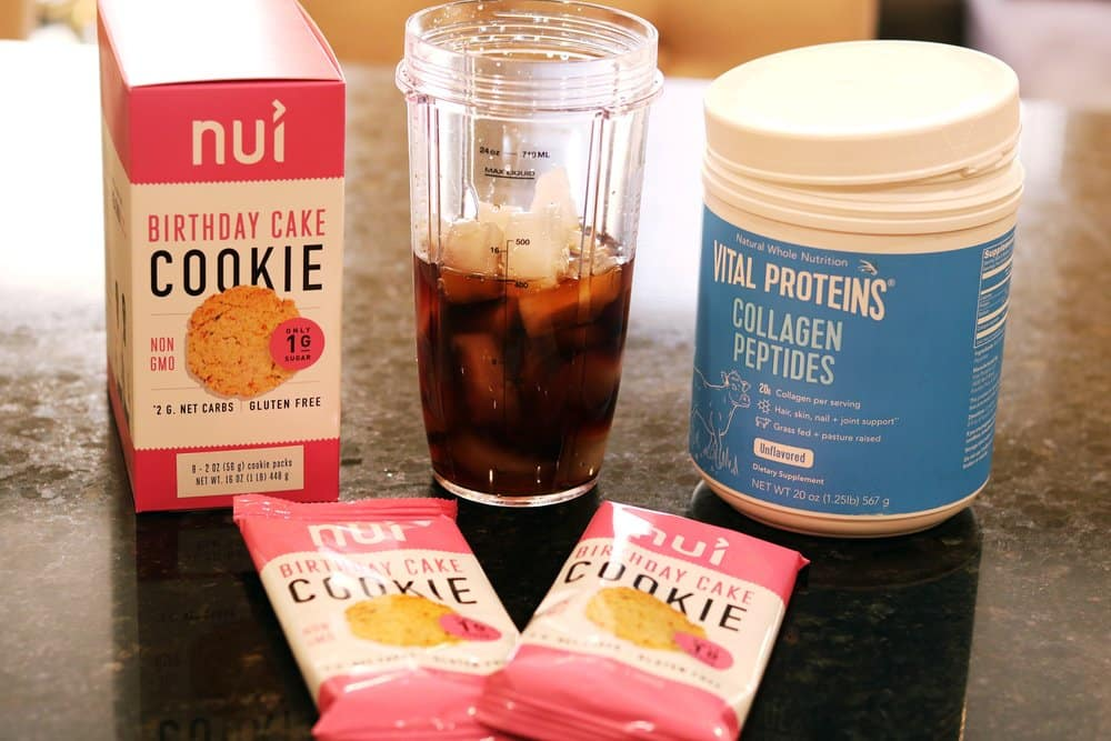 A blender cup of iced coffee next to a container of Vital Proteins\' Collagen Peptides, and surrounded by packs of birthday cake cookies