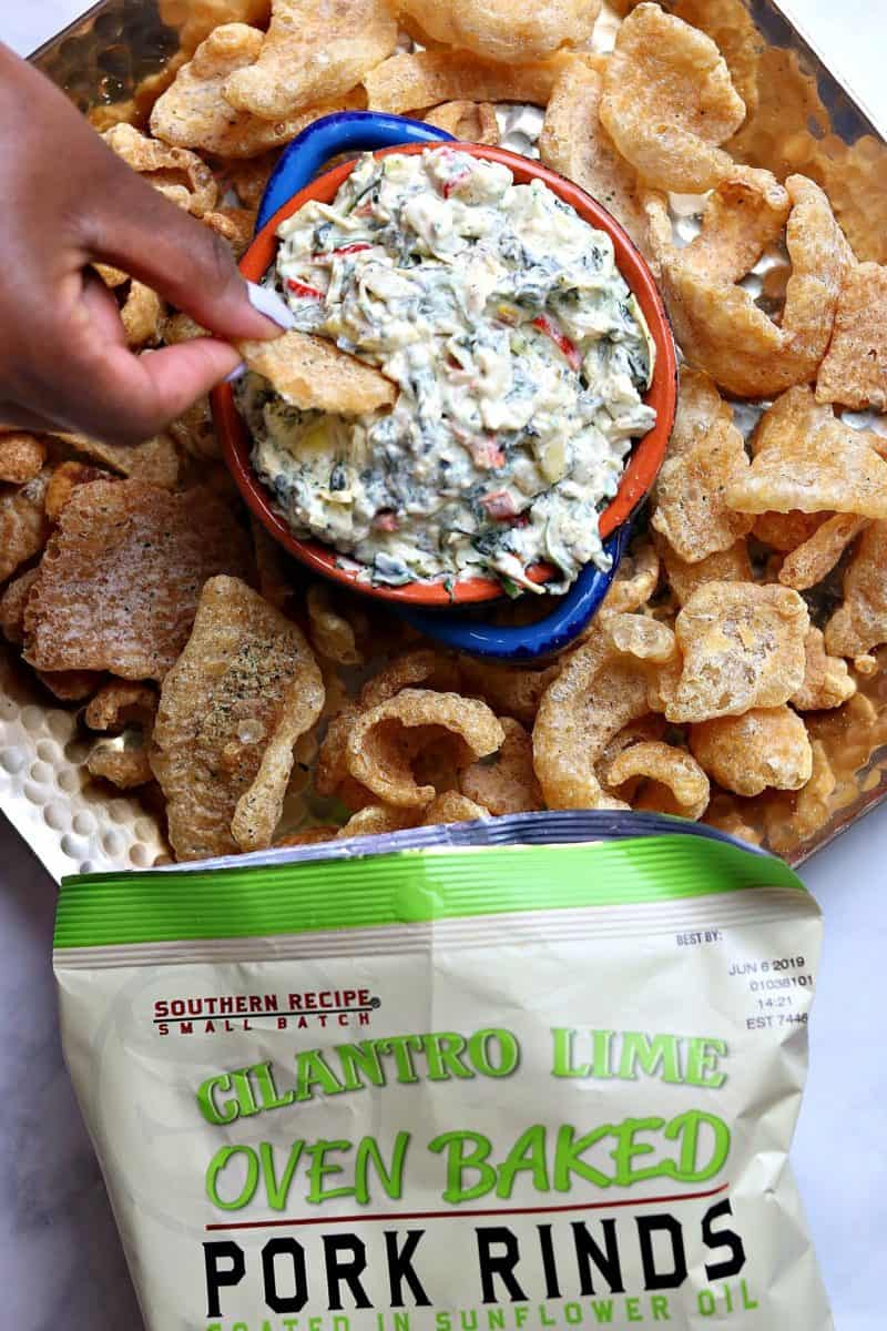 A bowl of Creamy Kale Artichoke Dip on a bed of Cilantro Lime Pork Rind.