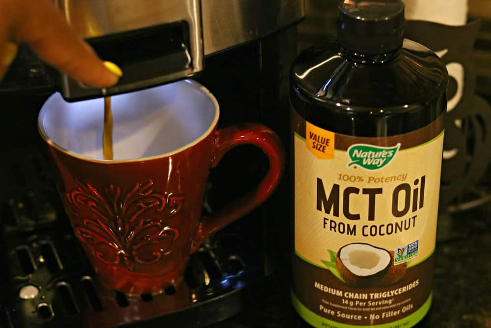 A bottle of Nature's Way MCT Oil next to a cup of coffee