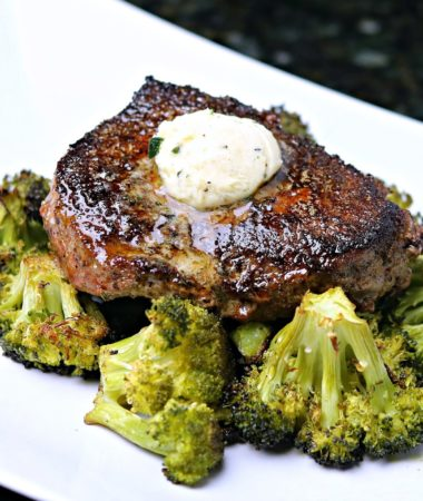 Ranch spiced steaks on top of a bed of broccoli on a white serving dish