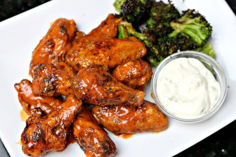 Keto Buffalo Wings on a plate with roasted broccoli and blue cheese dip