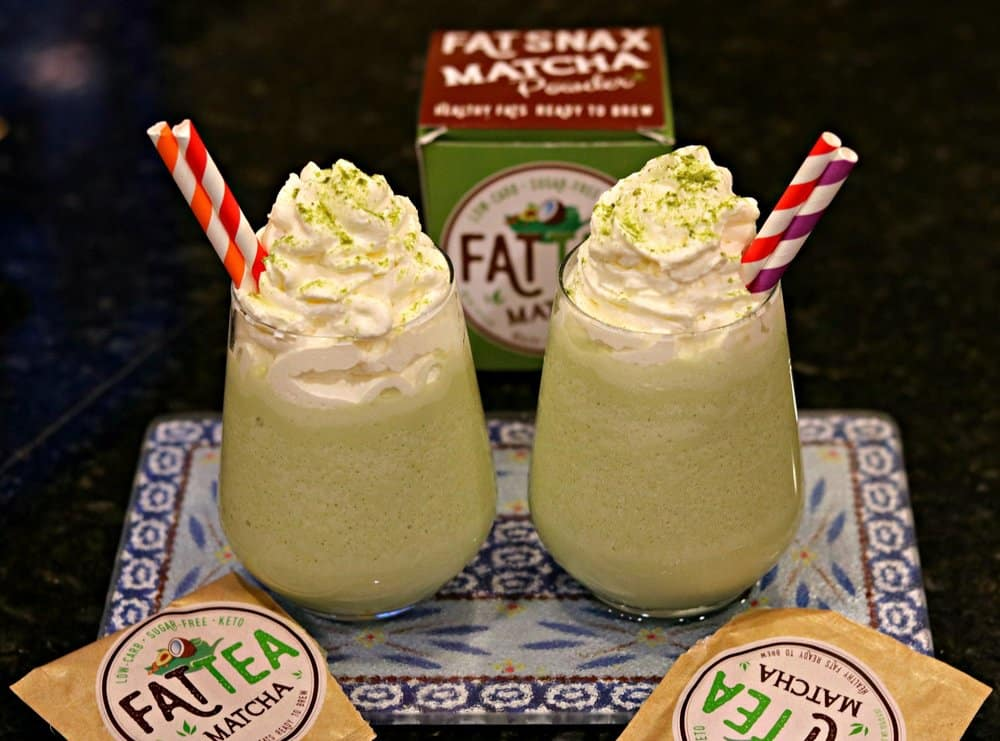 Two glasses of Keto Matcha (Green Tea) Creme Frappuccinos with red and white straws, and surrounded by Fat Snax products