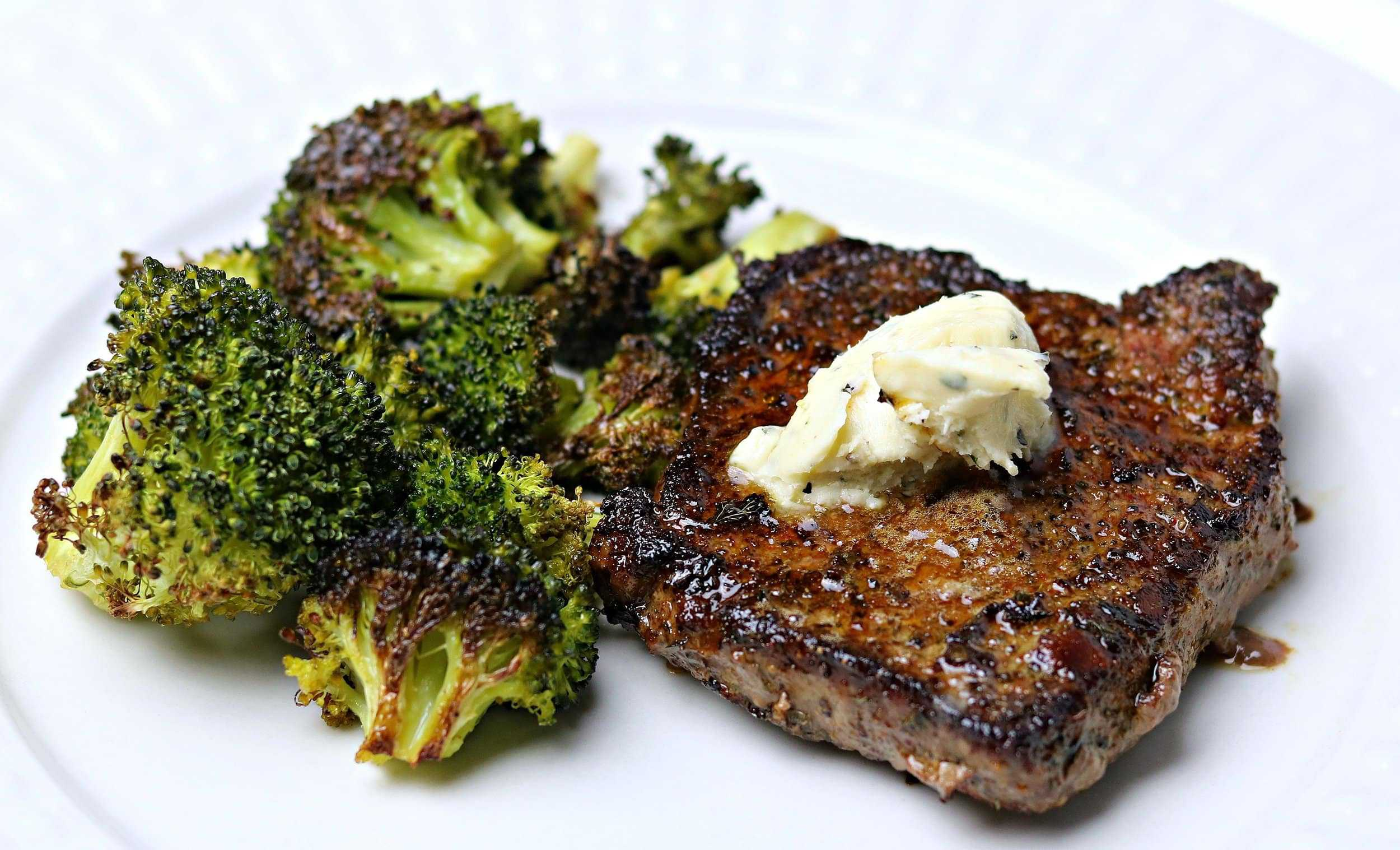 a close-up of beef sirloin steak on a plate with roasted broccoli and compound butter.
