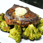 Top sirloin steak with melted butter on a plate with roasted broccoli.