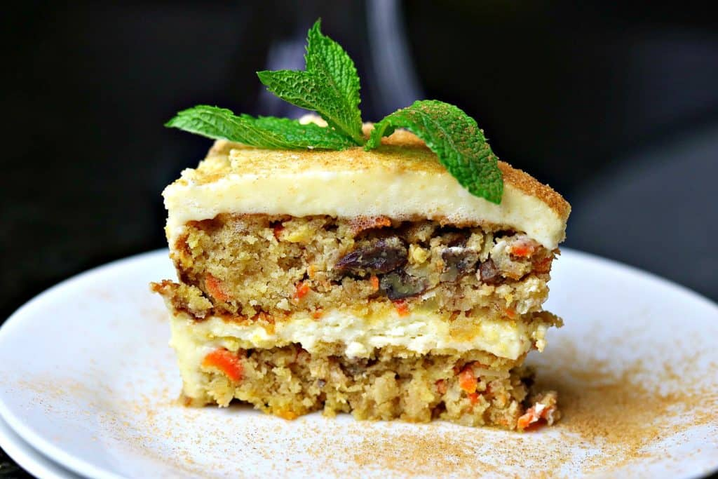 Double layer Low Carb Carrot Cake on a white plate with a mint leaf on top