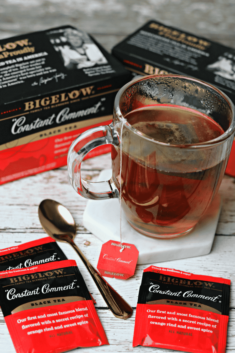 Two boxes of Bigelow Constant Comment Tea with a glass of tea and a golden spoon