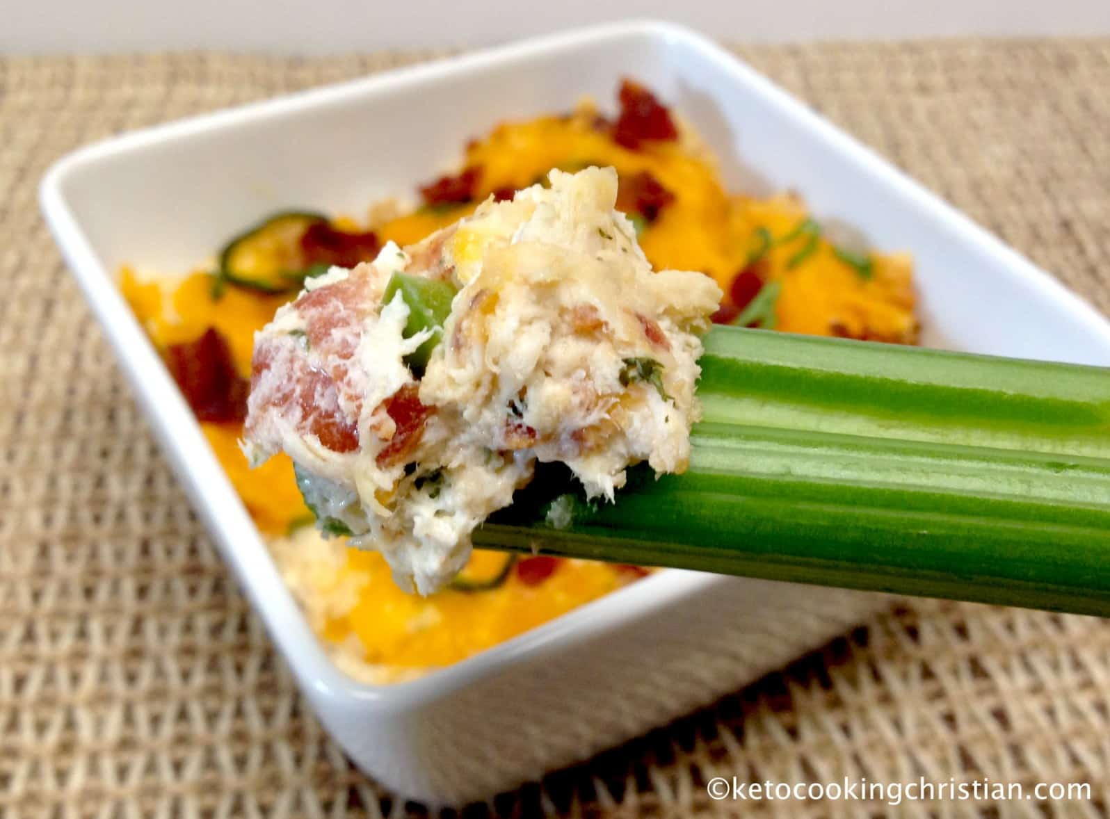 Low Carb Jalapeño Popper Dip in a white serving dish with a celery stick