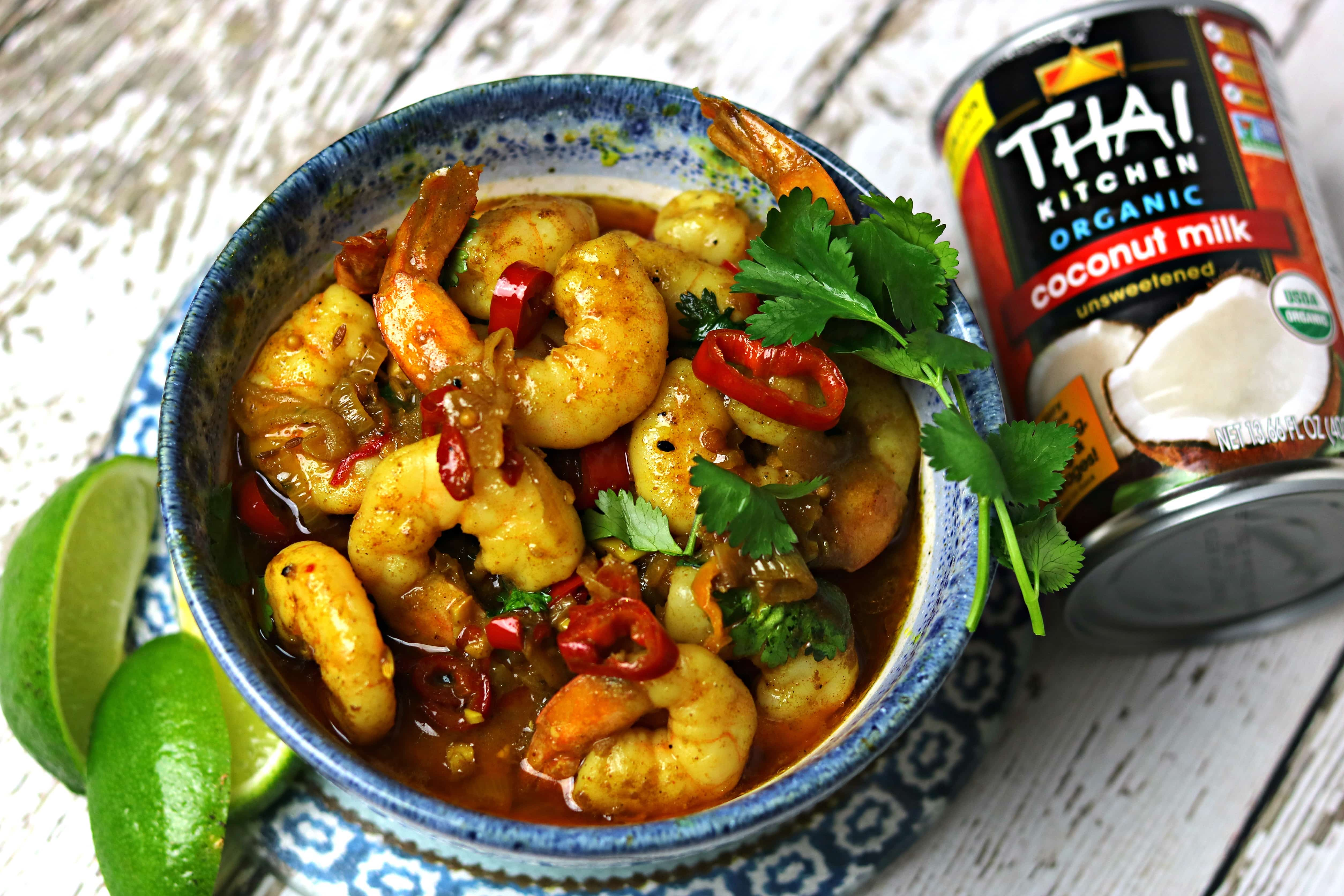 Indian Shrimp Curry recipe in a bowl with limes and coconut milk next to it