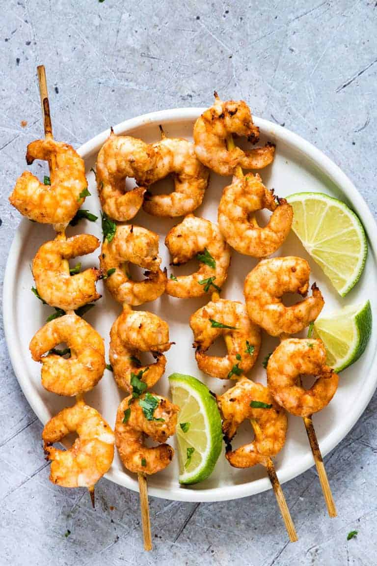 Cilantro Lime Shrimp Skewers on a plate with lime slices