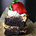 Two cheesecake brownies stacked on top of each other with a strawberry on top