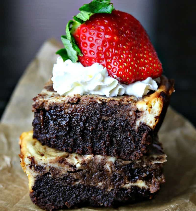 Two low carb cheesecake brownies stacked on top of each other with a strawberry on top