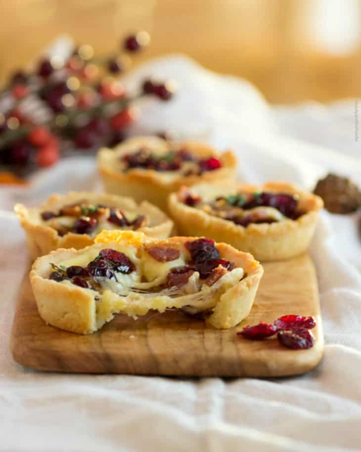 Savory Bacon Cranberry Cheese Tartlets on a wooden serving dish