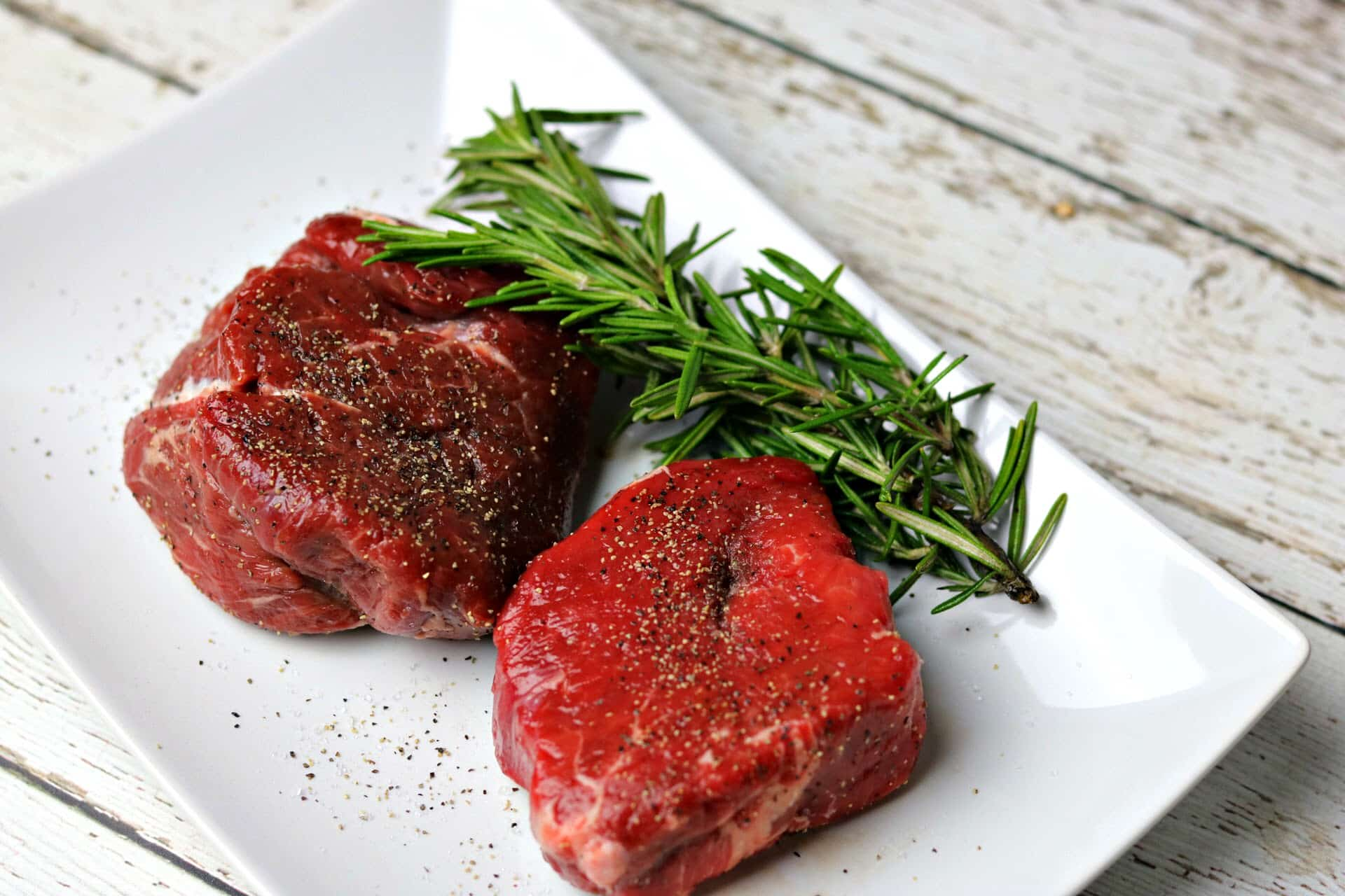 Two filet mignons on a plate with rosemary