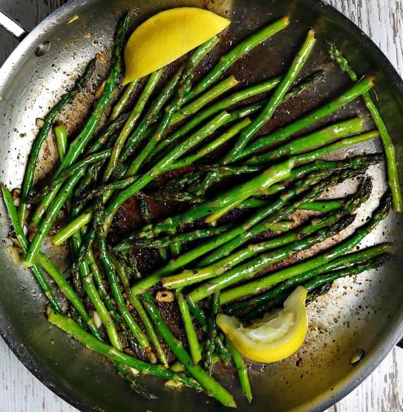 Sauteed asparagus in a frying pan with slices of lemon.