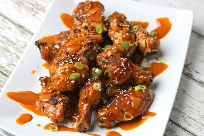 Red Curry Chicken wings on a plate topped with sesame seeds and sliced green onions