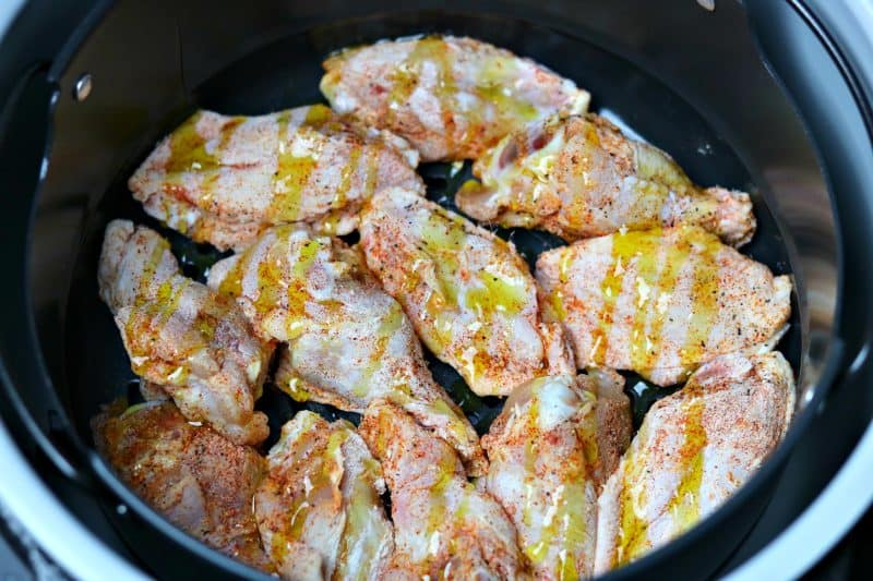 a close-up of thawed and seasoned chicken wings in the Ninja Foodi cooking pot
