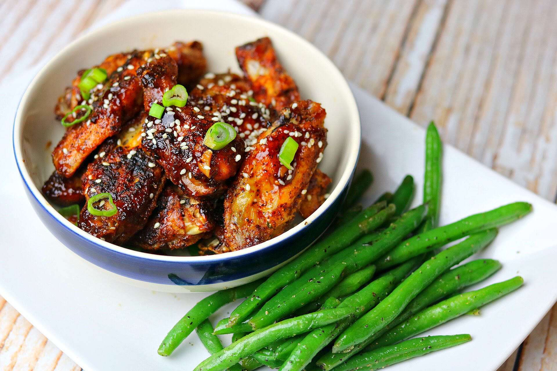 Keto Sweet Chili Wings on a plate with green beens