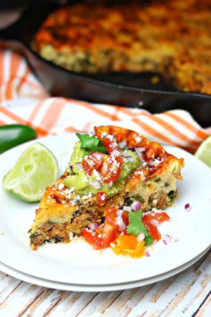 Baked Mexican Frittata on a plate with lime, salsa, and other toppings