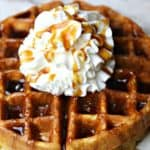 A close up of almond flour waffles on a plate topped with whipped cream and sugar-free maple syrup