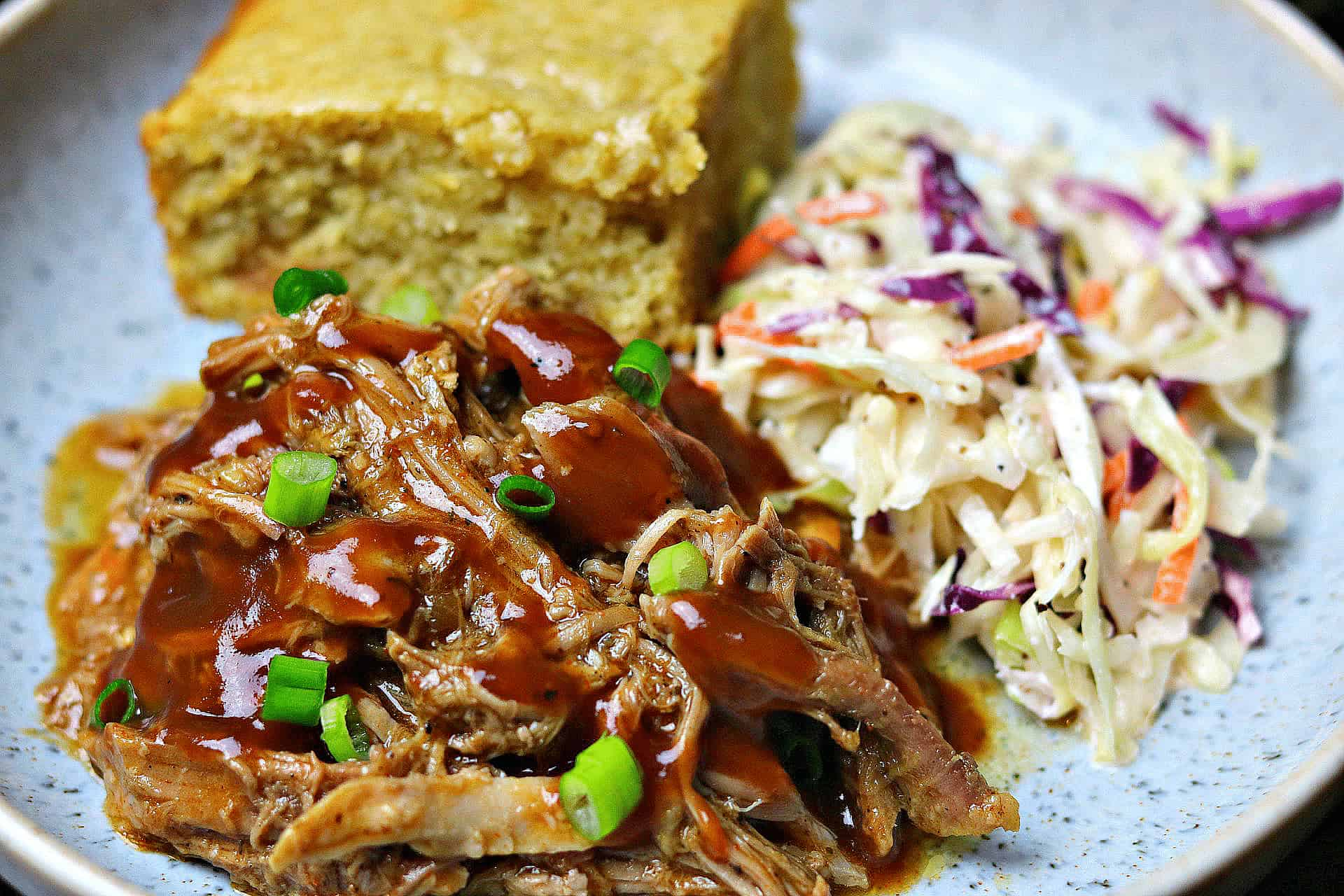 a close-up of Keto BBQ Pulled Pork on a plate with corn-free bread and keto coleslaw