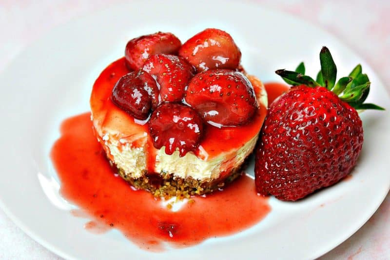 Gluten-free strawberry cheesecake on a plate with a strawberry and strawberry sauce