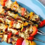 A stack of chicken kabob skewers on a blue serving dish.