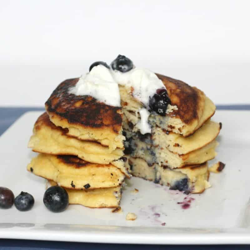 A stack of low carb blueberry pancakes on a white plate