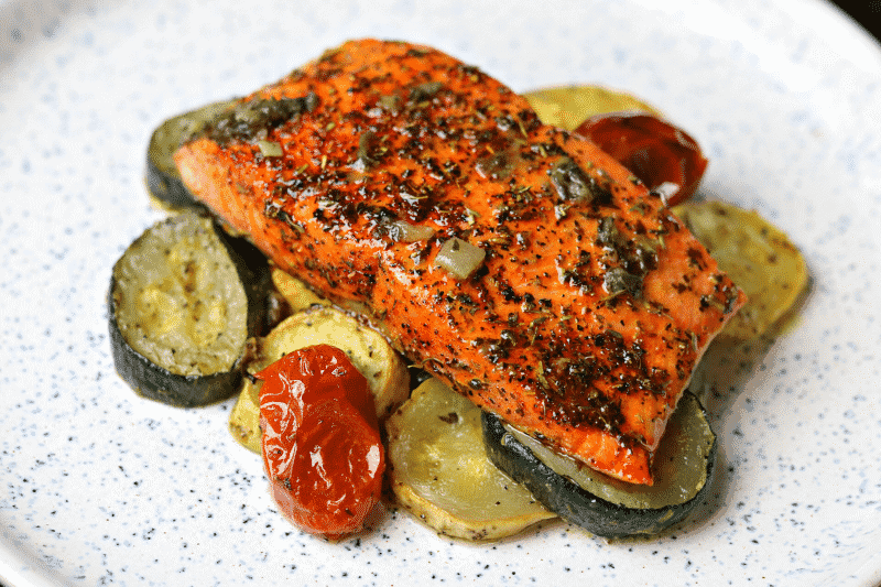 Air Fryer Salmon on top of a bed of Low-Carb Roasted Vegetables on a white serving dish.
