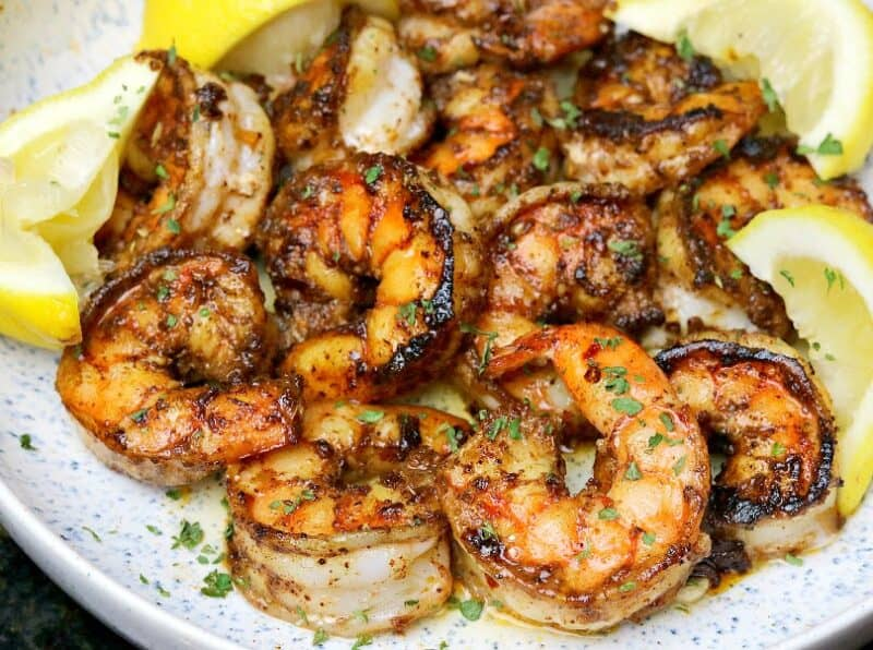 close-up of pan-seared shrimp in a bowl with lemons