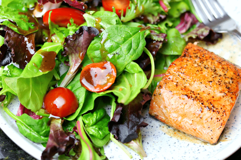 Salad with low-carb Balsamic Vinaigrette on a plate with salmon