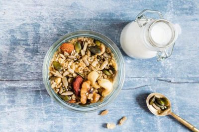 Low-Carb Granola in a glass serving bowl with milk and a spoon.