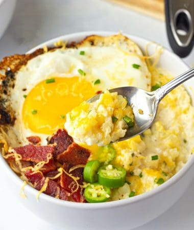 A bowl of food with Cheesy Cauliflower, an egg, jalapeño, and crispy bacon