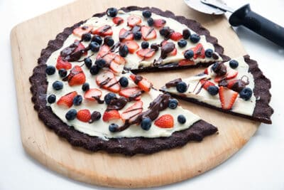 keto cookie pizza on a wooden pizza pan