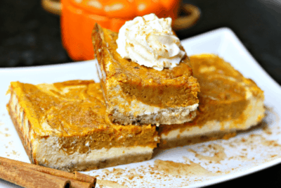 A stack of Keto Pumpkin Pie Cheesecake Bars on a white serving dish