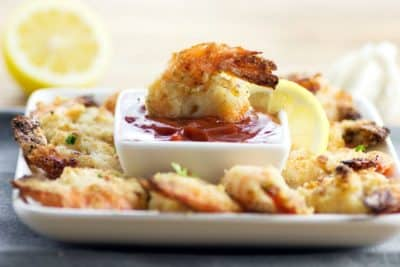 oven fried garlic shrimp on a serving dish with lemons and cocktail sauce