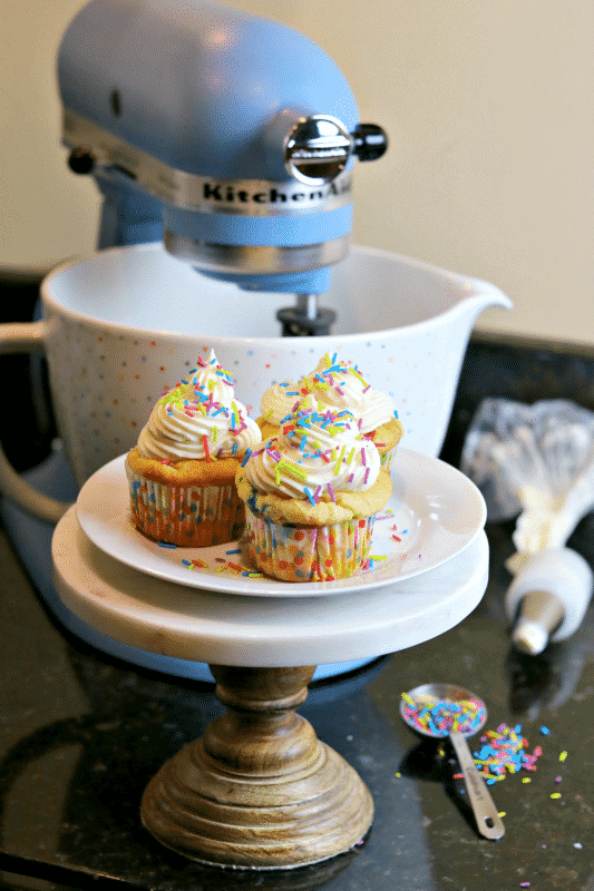 three Keto cupcakes on a stand with a KitchenAid stand mixer