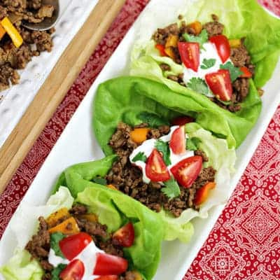 Three beef taco wraps on rectangular white plate