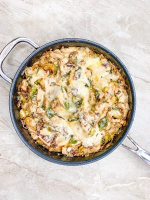 Cheese-topped Bacon Brussel Sprouts Chicken Casserole in a pan
