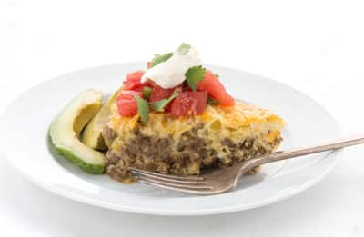 Taco Pie topped with tomatoes and sour cream on a plate with a side of sliced avocado