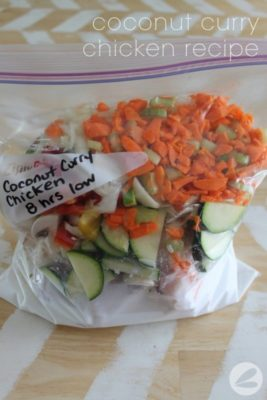 Freezer bag filled with cut zucchini, carrots, chicken, and other ingredients for Coconut Curry Chicken freezer meal