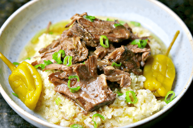 A bowl of Ninja Foodi pot roast with green onions, cauliflower rice risotto and gravy